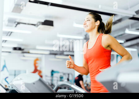 Beautiful young woman running on a treadmill in gym and smiling - Stock Photo