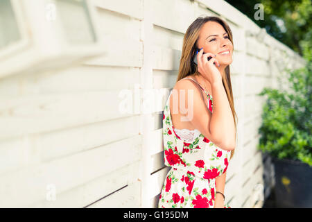 Beautiful young happy woman smiling during a phone call while leaning against a white wall - Stock Photo