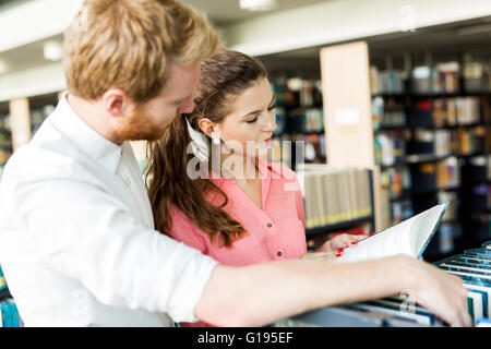 Two  smart students reading and studying in library whole searching through books on the shelves - Stock Photo
