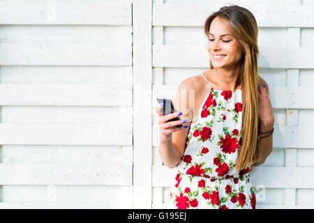 Beautiful young woman using phone while leaning against a white wall during a bright summer day - Stock Photo