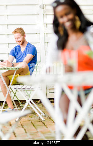 Handsome happy man holding phone in a cafe while sitting at a table outdoors - Stock Photo