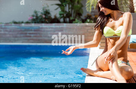 Young beautiful woman on the side of the pool playing with water displaying sensuality - Stock Photo