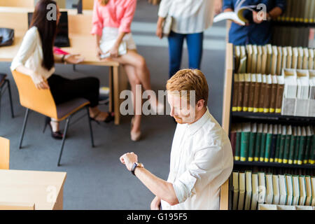 Group of young people preparing for an exame in a library and have no much time left. Deadline - Stock Photo