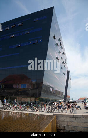 The Black Diamond housing the Royal Library at the waterfront in Copenhagen with its recreational area at the waterfront. - Stock Photo