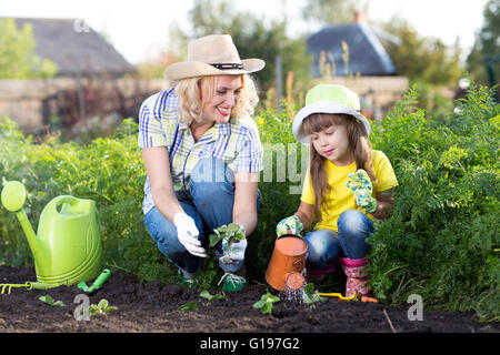 Mother and kid daughter planting strawberry seedling in a garden. Little girl watering new plants.