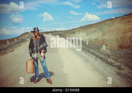 girl with a suitcase on the road - Stock Photo