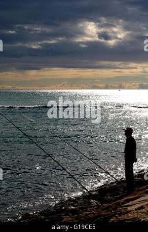Costa Blanca Spain Alicante city man fishing from the rocks Playa del Postiguet - Stock Photo