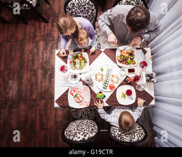 Family of four having meal at a restaurant - Stock Photo