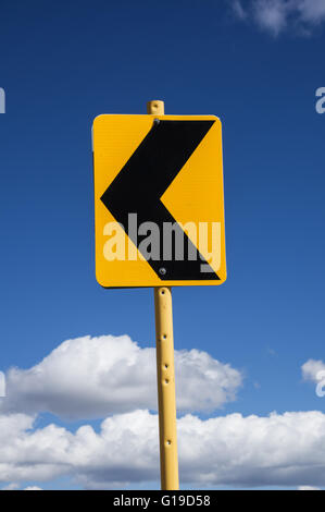 sign with black arrow pointing left warning of a curving road with blue sky and clouds background - Stock Photo