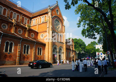 HO CHI MINH CITY, VIET NAM, Crowd of Vietnamese student in traditional dress, ao dai, Saigon Notre Dame Cathedral, - Stock Photo