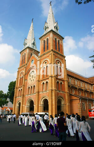 HO CHI MINH CITY, VIET NAM, Crowd of Vietnamese student in traditional dress, ao dai, at Saigon Notre Dame Cathedral, - Stock Photo