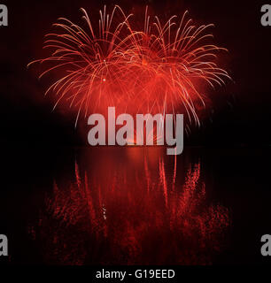Colorful fireworks with reflection on lake and night sky in background. - Stock Photo