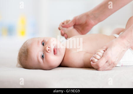 Baby 5 months massaging. Kid lying on the back - Stock Photo