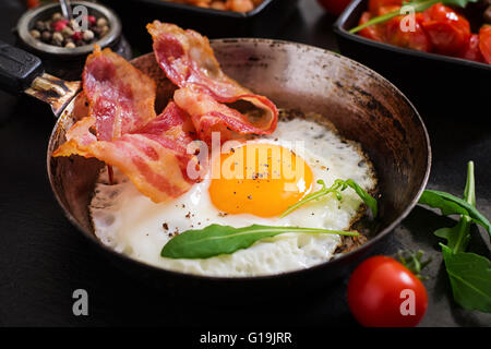 English breakfast - fried egg, beans, tomatoes, mushrooms, bacon and toast - Stock Photo