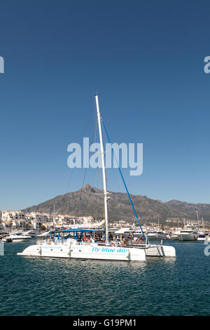 Catamaran sailboat sailing out of Puerto Banus harbour with Costa del Sol tourists, Marbella, Andalusia, Spain, - Stock Photo