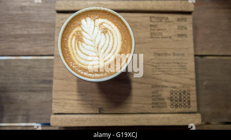 Coffee with white leaf latte art on wooden board - Stock Photo