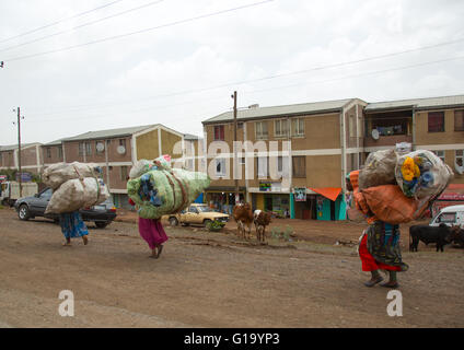 Ethiopian women carry heavy furnitures on their backs in front of new apartments blocks, Addis abeba region, Addis - Stock Photo
