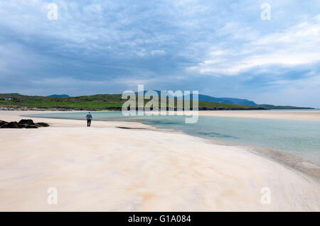 Lone walker on deserted empty beach on Loughros Point, Ardara, County Donegal, Ireland - Stock Photo