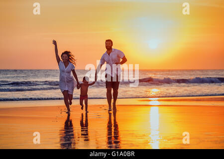 Happy family - father, mother, baby son hold hands and run with fun along sunset sea surf on black sand beach. - Stock Photo