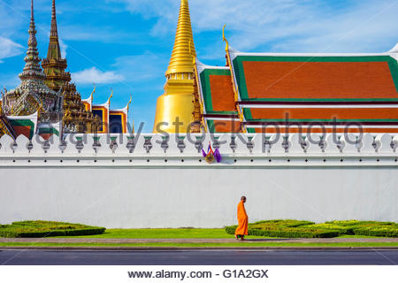 A monk passes in front of Wat Phra Kaew and the Grand Palace, Bangkok, Thailand - Stock Photo