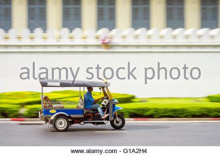 A Tuk-Tuk passes in front of the Grand Palace, Bangkok, Thailand - Stock Photo