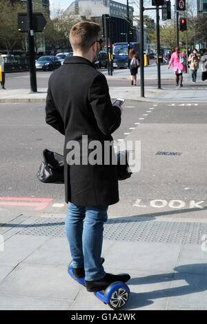 A young man checks his smartphone as he balances on an electric powered scooter board on the Euston Road, in London, - Stock Photo