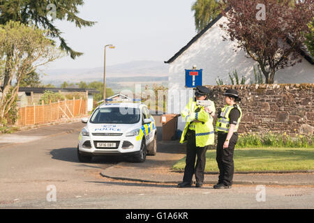 male and female police officers with hand held radar gun on a rural village road in Killearn, Stirlingshire, Scotland, - Stock Photo