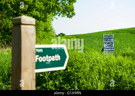 Footpath fingerpost pointing to sign in field saying this is private land, England UK - Stock Photo