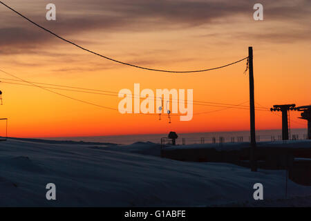 empty skilift in winter at sunset over the mountain in Ranca, Romania - Stock Photo