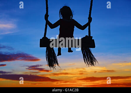 Black silhouette of baby girl flying high with fun on rope swing on blue orange sunset sky background. - Stock Photo