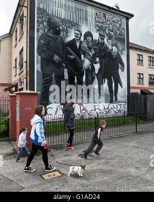 Local Catholic children passing the civil rights Bloody Sunday mural. Derry Londonderry. Northern Ireland. UK. Europe - Stock Photo