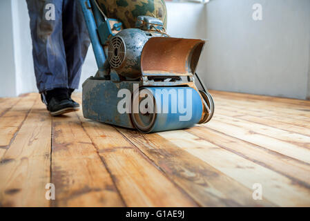 Worker polishing parquet floor with grinding machine - Stock Photo