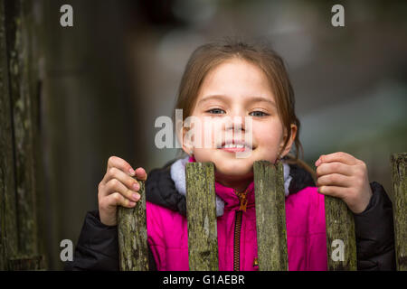 Portrait of little girl peeking from behind the fence. - Stock Photo