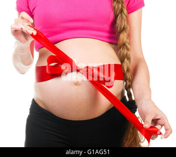 pregnant woman with red silk bow - Stock Photo