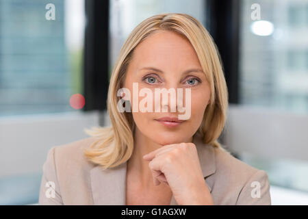 Portrait of businesswoman in modern office. Building in background. Looking at camera