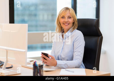 Smiling Middle aged business woman working in modern office. Looking at camera - Stock Photo