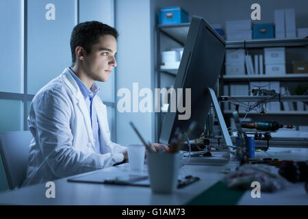 Confident engineering student working in the laboratory and using a computer, 3D printer in the background, technology - Stock Photo
