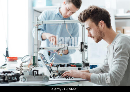 Engineering students working in the lab, a student is adjusting a 3D printer's components, the other one on foreground - Stock Photo