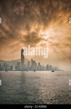 Skyline of Central, Hong Kong Island and Victoria Harbour with sun shining behind dramatic clouds, Hong Kong, China, - Stock Photo