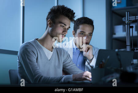 Students working at night in the lab, they are using a laptop, teamwork and education concept - Stock Photo