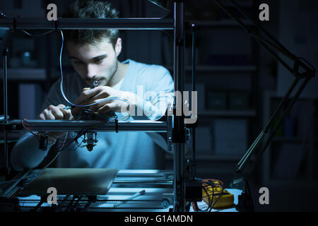 Young engineer working at night in the lab, he is adjusting a 3D printer's components, technology and engineering - Stock Photo