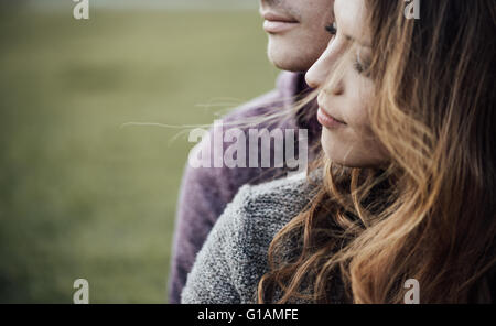 Young loving couple outdoors sitting on grass, hugging and looking away, future and relationships concept - Stock Photo