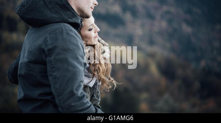Romantic young couple dating in winter, they are sitting together, she is leaning on her boyfriend's shoulder - Stock Photo