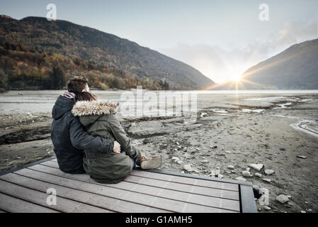 Loving couple sitting on a pier, hugging and looking away, love and feelings concept - Stock Photo