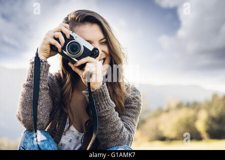 Young female photographer sitting on the grass and taking pictures, natural landscape on background - Stock Photo
