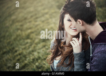 Young loving couple sitting on grass, she is flirting with him, love and relationships concept - Stock Photo