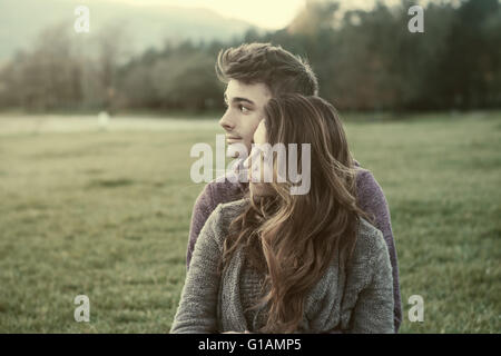 Young teenagers outdoors, sitting on the grass and cuddling, he is hugging his girlfriend, relationships and feelings - Stock Photo