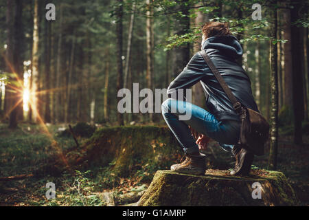Young handsome man exploring the forest and looking around, nature and freedom concept - Stock Photo