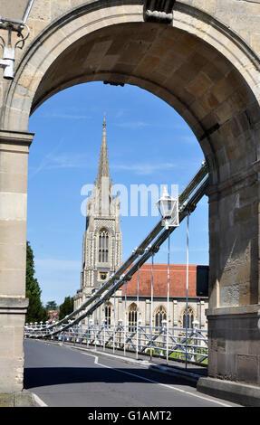 Bucks - Marlow on Thames - view through imposing 19c suspension bridge arch - framing All Saints church - sunlight - Stock Photo