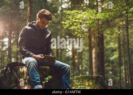 Young handsome man sitting in the woods and using a digital touch screen tablet, wi-fi connection and freedom concept - Stock Photo